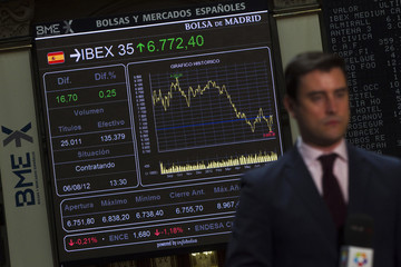 A television reporter does a stand up next to an electronic board at Madrid's Bourse