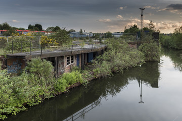 An old, derelict, building, beside a calm canal, overgrown with foliage, set in a urban wasteland, reflected on the very still water, in Birmingham, England