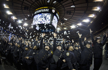 New York Police graduates throw their white gloves up in the air following their induction ceremony at Madison Square Garden in New York