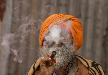 A Sadhu smokes cannabis at a makeshift shelter on banks of river Ganges on his way to an annual trip to Sagar Island, in Kolkata