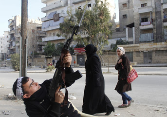 A woman looks at an armed member of the Free Syrian Army while he poses for the camera in Al-Ansari area, Aleppo