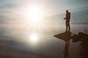 Mann mit Kaffeebecher genießt den Sonnenaufgang am See