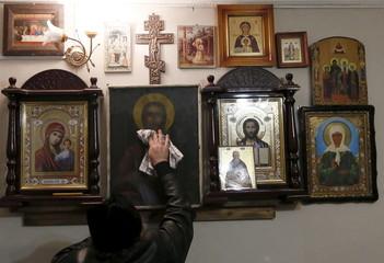 Orthodox priest Ryzhov removes dust from icons at his house in the village of Bolshaya Murta north of Krasnoyarsk