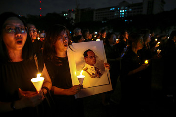 A mourner holds up a picture of Thailand's late King Bhumibol Adulyadej as she gathers with others during a vigil to mark his birthday, at a university in Bangkok