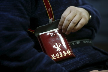 Seo Jae-pyoung, the secretary general of the association of the North Korean defectors, poses for a photograph while demonstrating the use of a Workers' Party membership card holder during an interview with Reuters in Seoul