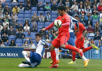 Barcelona's Luis Suarez controls the ball against Espanyol's players during their Spanish first division soccer match at Power8 stadium in Cornella de Llobregat near Barcelona