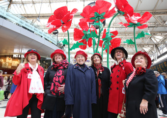 Members of the war widows association pose for a photograph in front of a poppy sculpture in Waterloo station