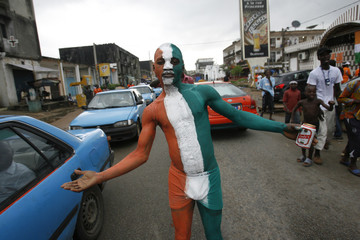 An Ivory Coast fan painted in the colours of the Ivory Coast flag poses before their 2010 World Cup soccer match against Brazil, in Abidjan