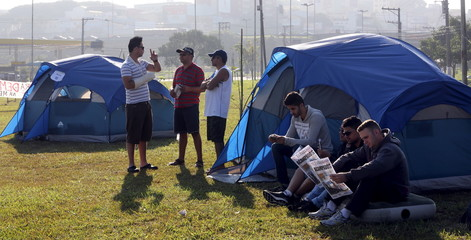 Mercedes Benz workers read newspapers at a camp in front of the Mercedes-Benz plant in Sao Bernardo do Campo as they protest against the dismissal of 500 workers in May