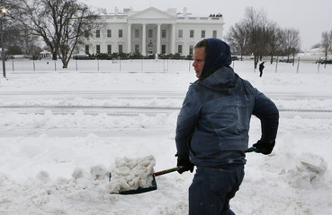 Peace activist Knight clears snow at a peace vigil tent along Pennsylvania Avenue in front of the White House after the region was pounded with snow overnight around Washington