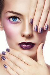 Close-up portrait of young beautiful woman with stylish make-up and glitter manicure