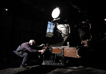 Puffing Billy maintanence worker pulls the coupler of steam locomotive 12A before being assigned to a passenger train at Belgrave station near Melbourne