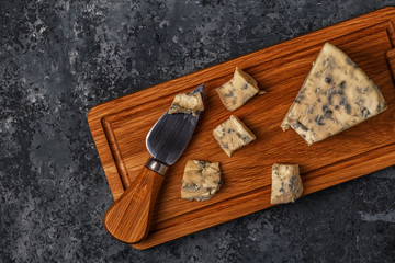 Pieces of blue cheese on wooden serving board.