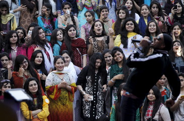 College girls listen to the music of Bhangra musician Sukhbir Singh at a spring festival in Islamabad