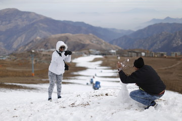 Colombian tourists take pictures at the El Colorado ski centre at Los Andes Mountain range, near Santiago