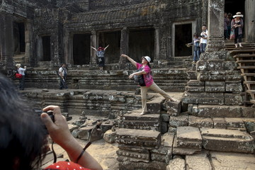 Tourists pose for pictures at Angkor Thom in Siem Reap