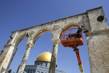 The Dome of the Rock is seen in the background as a Palestinian labourer repairs a light on a wall during preparations ahead of Ramadan in Jerusalem's Old City
