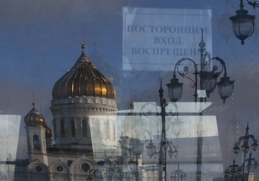 """Sign reading """"No trespassing"""" is seen posted on glass door as Christ the Saviour Cathedral is reflected on it, in Moscow"""
