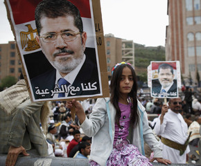A girl holds a poster of Egypt's deposed Islamist President Mohamed Mursi during a rally in protest of the recent violence in Egypt, in Sanaa