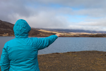 Woman in a blue jacket with her back to the photographer on the coast of huge cold lake on the stony rocky desert landscape of Iceland
