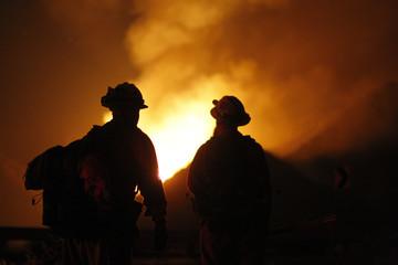 Members of an inmate hand crew look at flames at the Falls Fire west of Lake Elsinore, California.