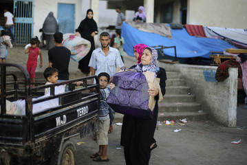 A Palestinian family leaves a United Nations-run school sheltering displaced Palestinians, before making their way home after a ceasefire was declared, in Khan Younis in Gaza Strip
