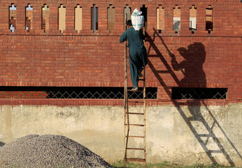 A laborer carries a sack of gravel up a ladder to the roof of a house under construction in Islamabad