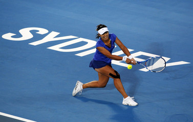 Li Na of China returns the ball to Kim Clijsters of Belgium during the women's singles final at the Sydney International tennis tournament