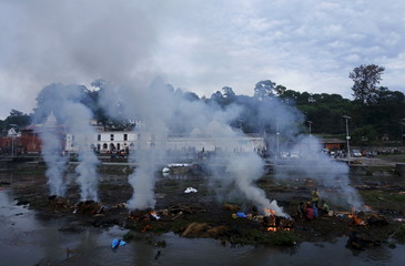 Relatives sit amidst the burning pyres of their family members, who died in Saturday's earthquake, during a cremation along a river in Kathmandu