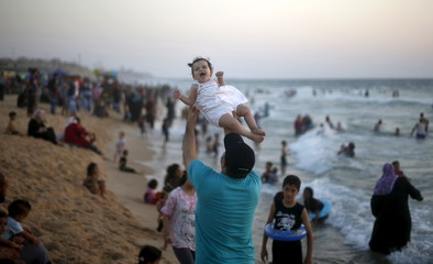 Palestinian man lifts his daughter as he enjoys the warm weather with his family on a beach along the Mediterranean Sea in the northern Gaza Strip