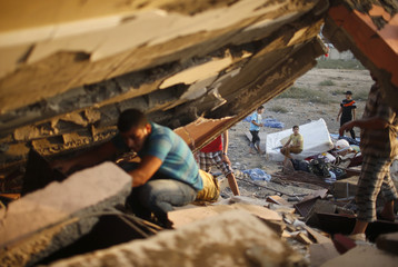 Palestinian man searches for belongings under the rubble of a house which police said was destroyed in an Israeli air strike in Gaza City