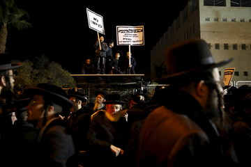 Ultra-Orthodox Jews hold signs during a protest in Jerusalem