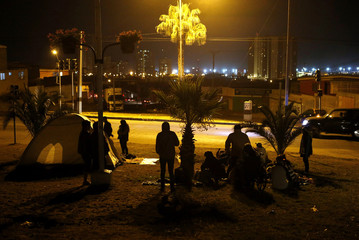 People stay on higher grounds after an earthquake and tsunami hit the northern port of Iquique