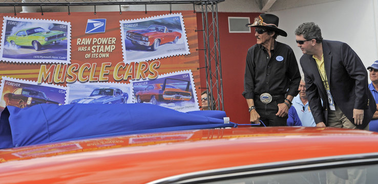 U.S. Postmaster General Donahoe looks on as racing legend Petty unveils the new Muscle Cars Forever stamps at a dedication ceremony at the Daytona International Speedway