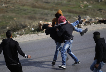 An injured stone-throwing Palestinian protester is carried during clashes with Israeli soldiers near Ramallah