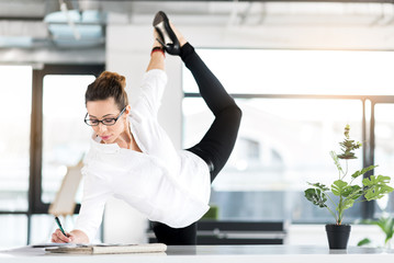 Outgoing secretary doing gymnastic exercise in office