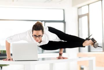 Smiling flexible woman watching at laptop