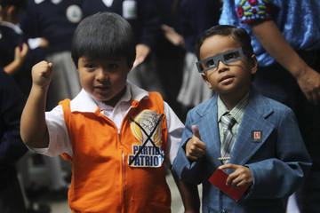 Boys dressed as Guatemala's presidential candidates Patriot Party's Molina and Libertad Democratica Renovada's Baldizon gesture during a symbolic vote for children inside the Maria Auxilio de Cristianos school in Guatemala city