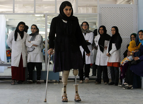 A disabled Afghan woman exercises with her prosthetic legs at the Orthopedic Center of the International Committee of the Red Cross in Kabul