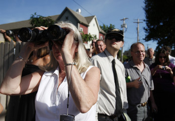 A woman in a crowd of on-lookers uses a pair of binoculars to scan a crowd of guests loading onto a bus heading for Chelsea Clinton's wedding in Rhinebeck