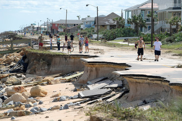 Onlookers walk past a washed out portion of State Highway A1A in the aftermath of Hurricane Matthew in Flagler Beach