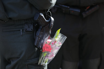 Police officer with flowers in pocket stands guard during Rose Monday carnival parade in Duesseldorf