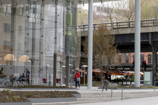 People walk from the High Line across a courtyard to The Whitney Museum of American Art in New York