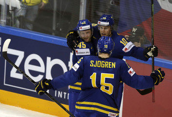 Sweden's Lindstrom celebrates his goal against the Czech Republic with team mates Moller and Sjogren during their Ice Hockey World Championship game at O2 arena in Prague