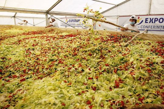 Volunteers mix vegetables to create the world's biggest vegetable salad during a Guinness World Record attempt in Pantelimon