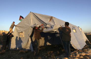 Palestinians arrange a newly-erected tent in the West Bank village of Beit Iksa, between Ramallah and Jerusalem