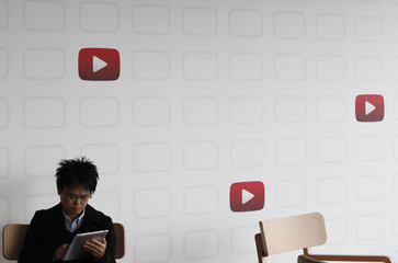 A man uses an Apple iPad tablet in front of a wall featuring the play icons of YouTube at the YouTube Space Tokyo, operated by Google, in Tokyo