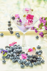 Glass goblet  with a refreshing drink, around many different berries blueberries and blueberries and ice cubes. Summer holiday mood. A light photo with a soft selective focus.