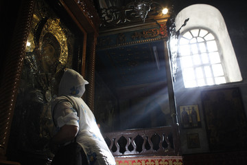 A tourist kisses a picture of the Virgin Mary as she visits visits the Church of the Nativity in Bethlehem