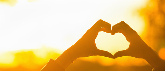 Silhouette hand heart shape with sun light
